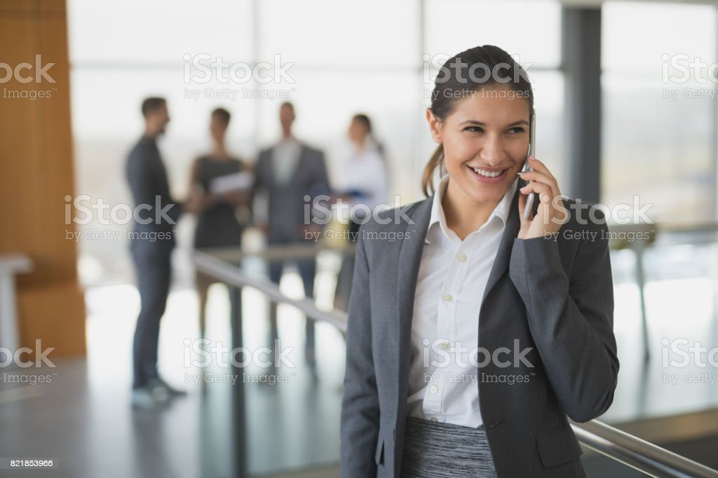 Young businesswoman using mobile phone in office building hallway. stock photo