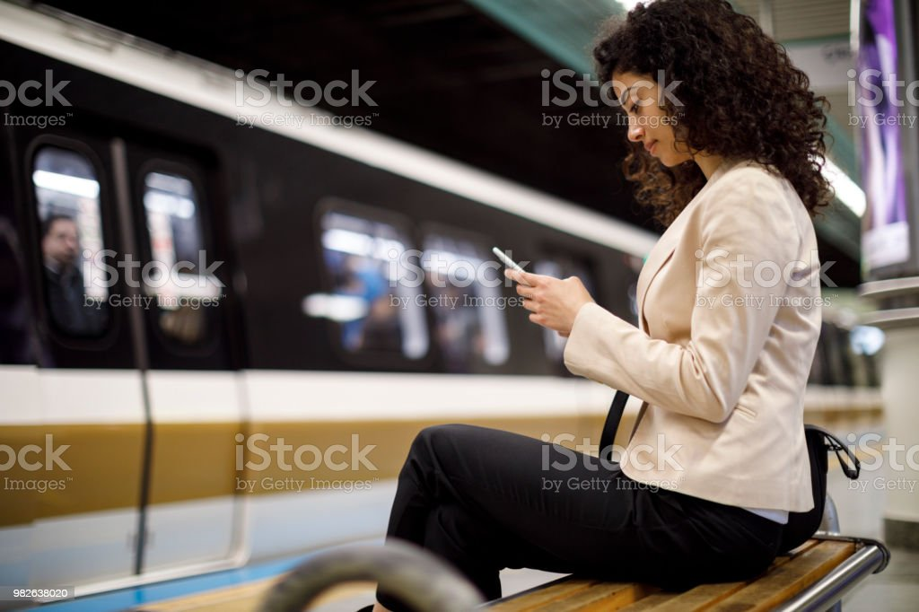 Young businesswoman using mobile phone while waiting for the train on...