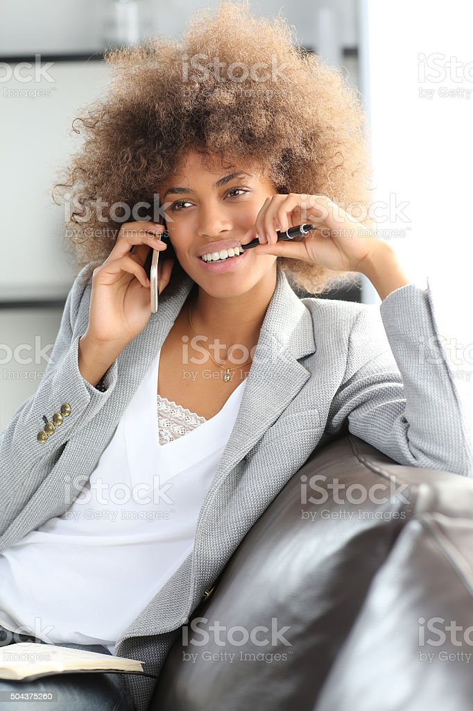 young businesswoman using phone to make appointment stock photo