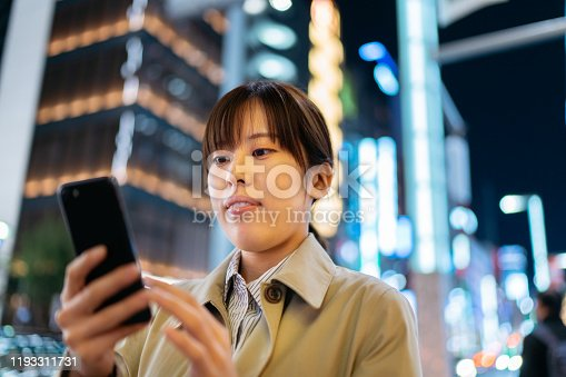 A young businesswoman commuter is using a smart phone to order a transportation in the street at night.