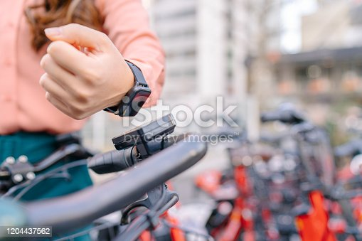 A young businesswoman is using her smart watch to rent a sharing bicycle.