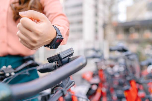 スマートウォッチを使用して自転車を借りる若いビジネスウーマン - sustainability ストックフォトと画像