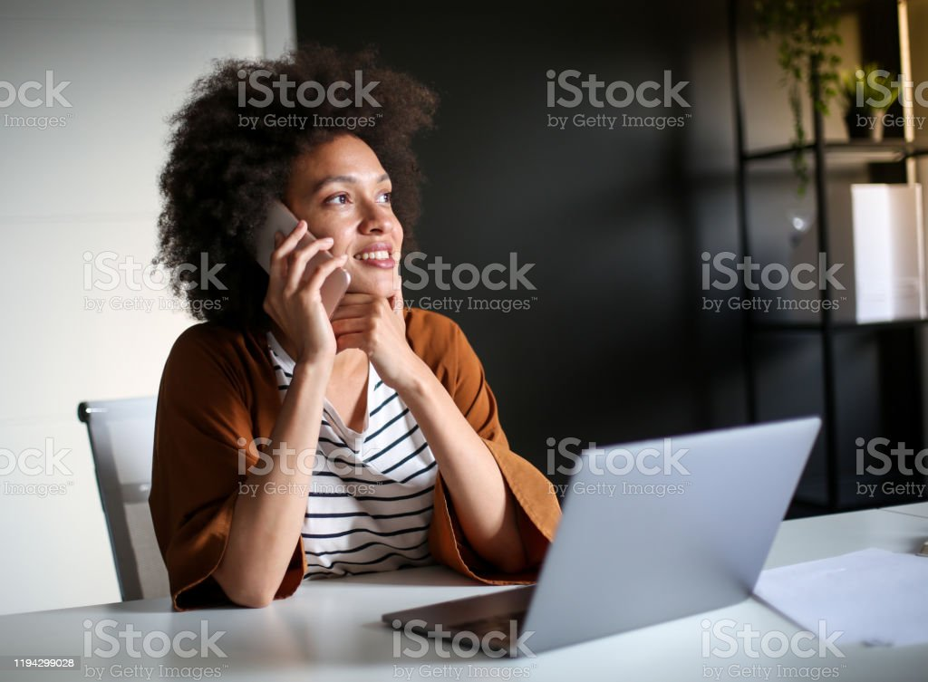 Young businesswoman using smartphone in he office. Young attractive African American businesswoman having a conversation with client about market research while sitting in the office. 20-29 Years Stock Photo