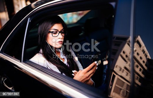 istock Young businesswoman using smartphone sitting in black limousine 907991392