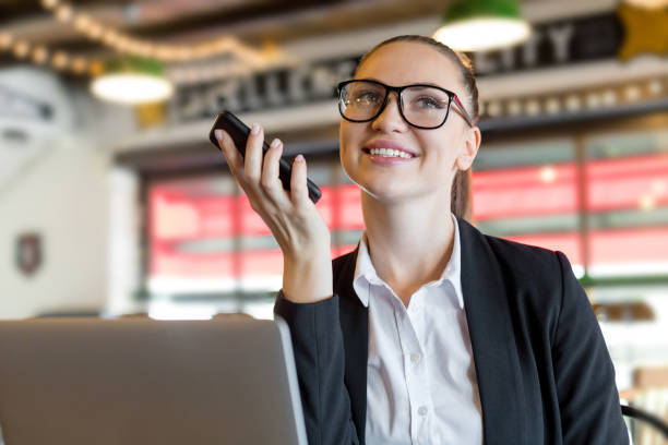 young businesswoman using the voice recognition of the phone - dictaphone stock pictures, royalty-free photos & images