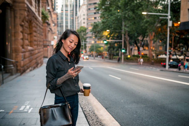 Young businesswoman waiting for taxi in Sydney Young businesswoman waiting for taxi in Sydney. She has a coffee to go. vietnamese ethnicity stock pictures, royalty-free photos & images