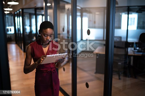 Young businesswoman walking with digital tablet at coworking