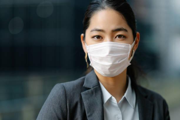 市内でフェイスマスクを着用した若いビジネスウーマン - くしゃみ 日本人 ストックフォトと画像
