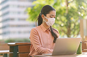 A young businesswoman is wearing a face mask to be protective from viruses in the city.
