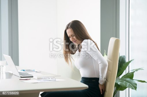 istock Young businesswoman with a backpain 627233020