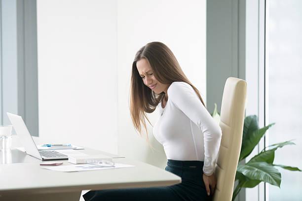 young businesswoman with a backpain - rückenschmerzen beim sitzen stock-fotos und bilder