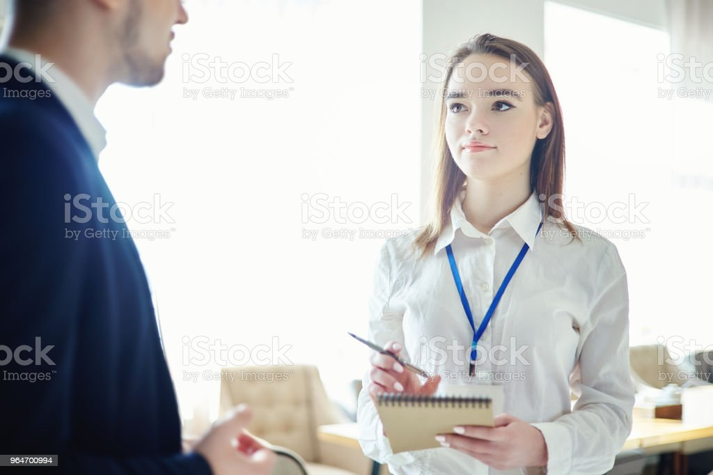 Young businesswoman with accreditation badge around her neck talking to unrecognizable male colleague. Female professional networking at business conference royalty-free stock photo