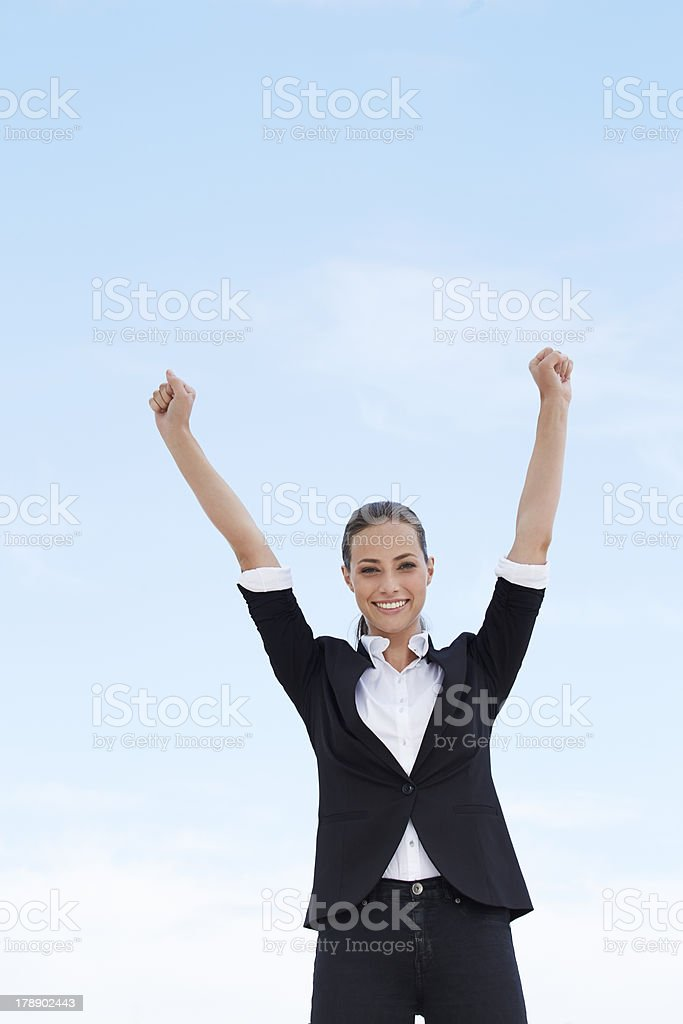 Young businesswoman with arms up against blue sky royalty-free stock photo