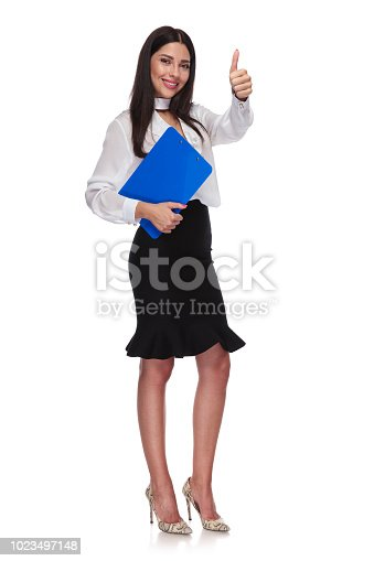 istock young businesswoman with blue clipboard makes ok sign 1023497148