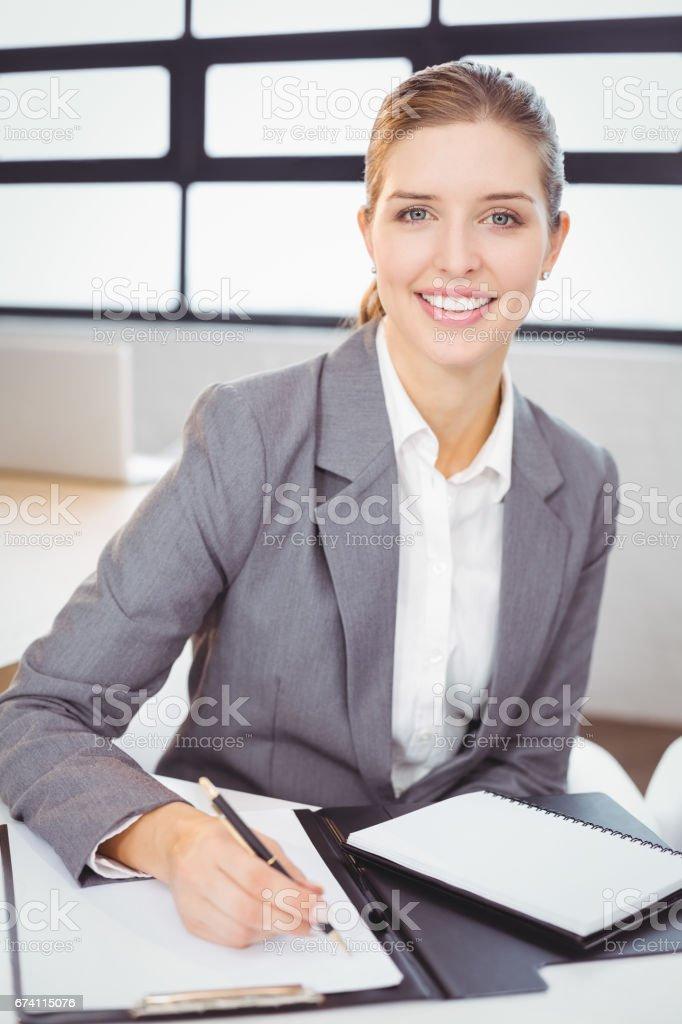 年輕女商人與坐在辦公桌前的檔 免版稅 stock photo