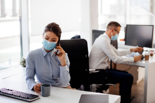 Young businesswoman with face mask talking on the phone in the office stock photo stock photo