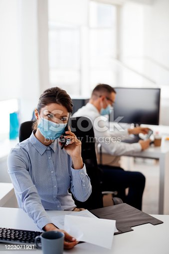 Young businesswoman with face mask talking on the phone while working in the office. stock photo. Shadow DOF. Developed from RAW; retouched with special care and attention; Small amount of grain added for best final impression. 16 bit Adobe RGB color profile.