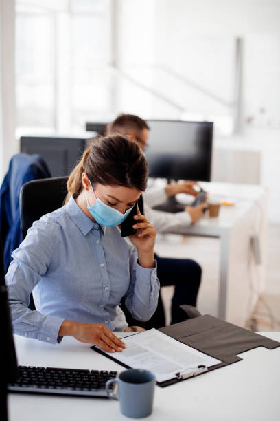 Young businesswoman with face mask talking on the phone while working in the office. stock photo stock photo