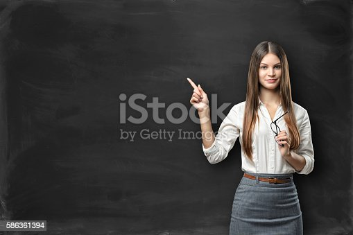 istock Young businesswoman with glasses in hand pointing at blank blackboard 586361394