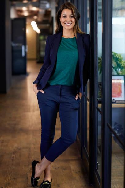 young businesswoman with hands in pockets - appoggiarsi foto e immagini stock