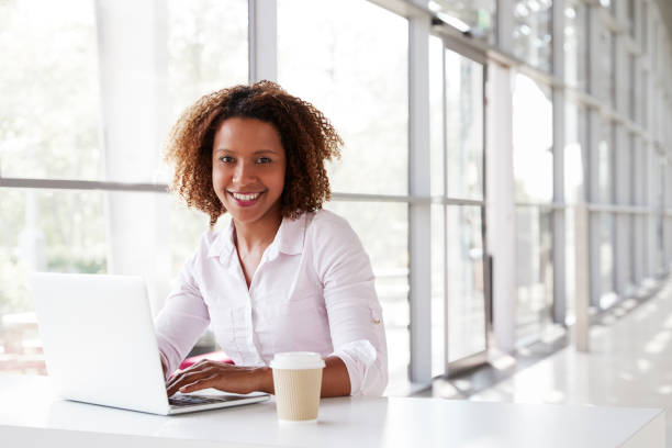 Young businesswoman with laptop at desk looking to camera stock photo