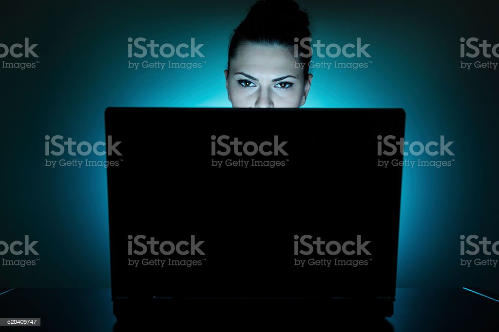 Young businesswoman with laptop at night stock photo