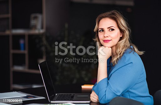 Young beautiful businesswoman with laptop sitting in an office, looking at camera.
