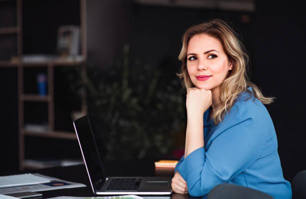 Junge Geschäftsfrau mit Laptop sitzt in einem Büro und schaut in die Kamera. – Foto