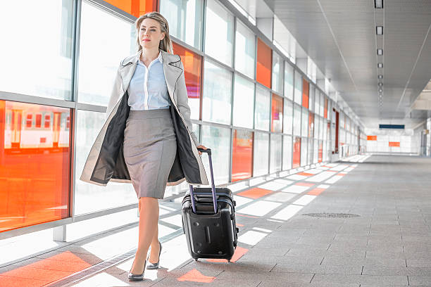 young businesswoman with luggage walking in railroad station - business travel stock photos and pictures