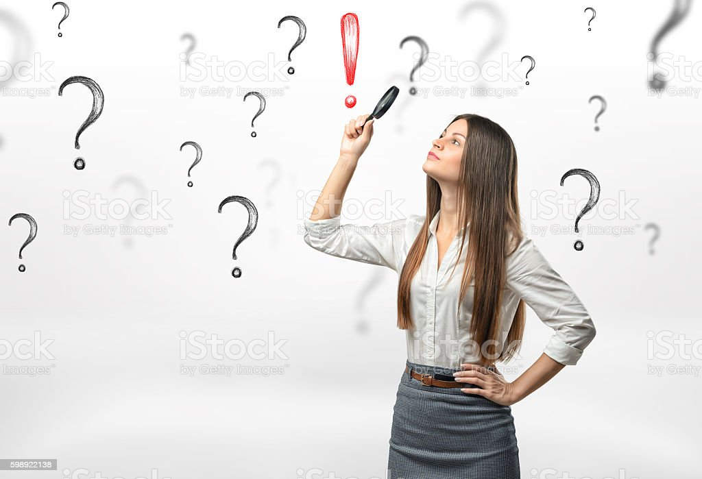 Young businesswoman with magnifying glass over her head looking at stock photo