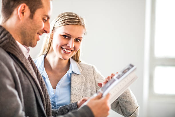 Young businesswoman with male colleague reading brochure in office – Foto