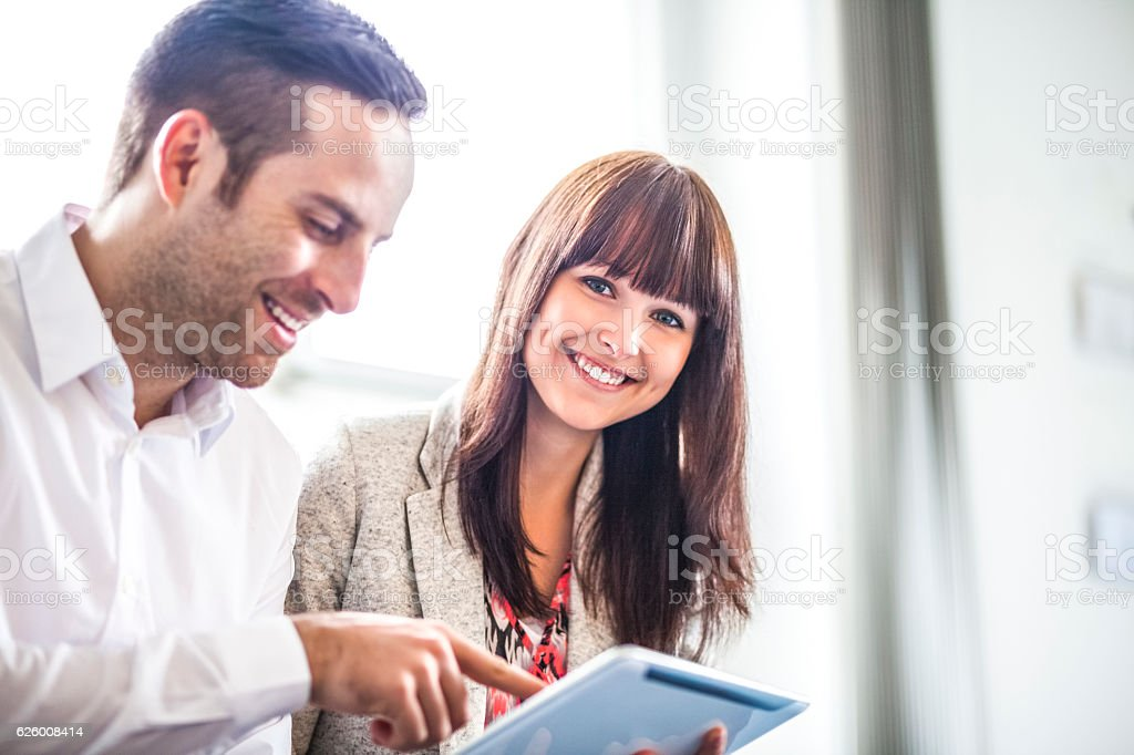 Young businesswoman with male colleague using digital tablet in office – Foto