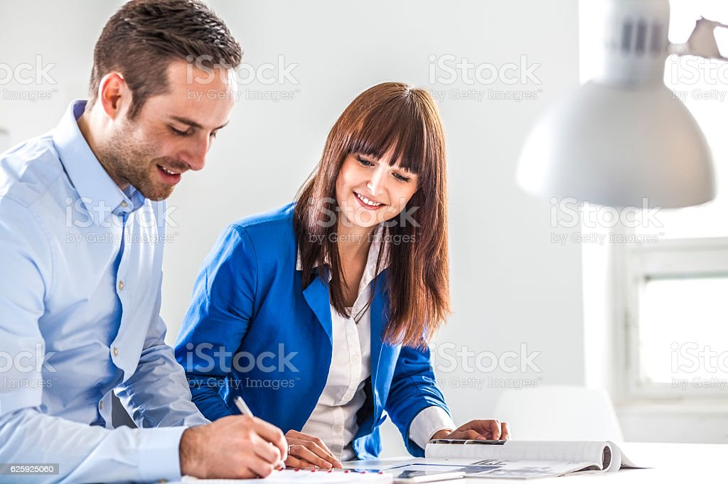 Young businesswoman with male colleague working together in office - Lizenzfrei Arbeiten Stock-Foto
