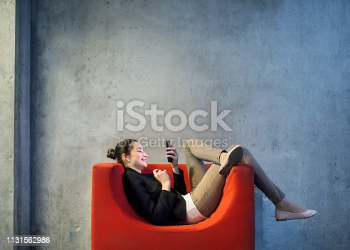 A young businesswoman with smartphone sitting on red armchair in office, a gray concrete wall in the background.