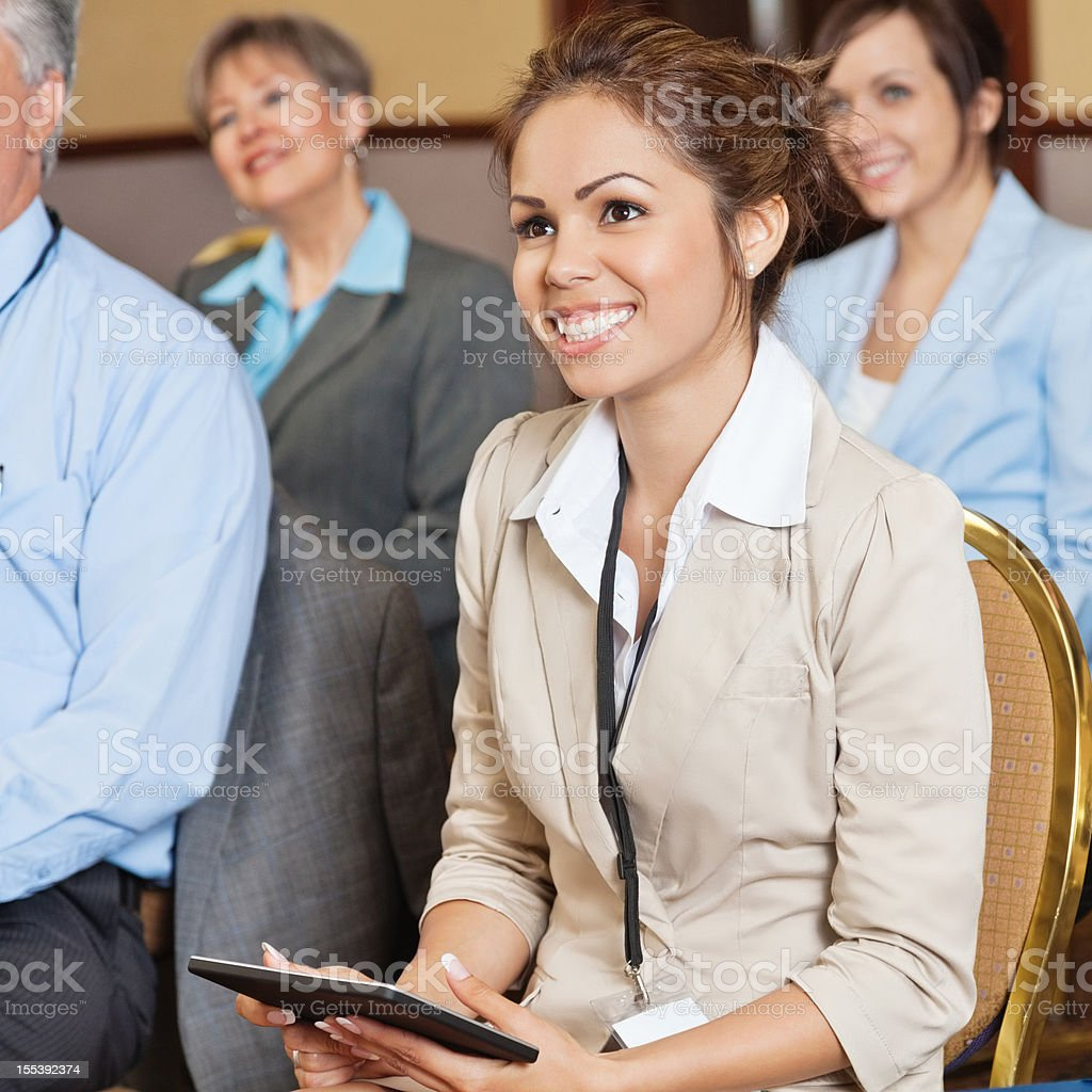 Young businesswoman with tablet listening during business presentation royalty-free stock photo
