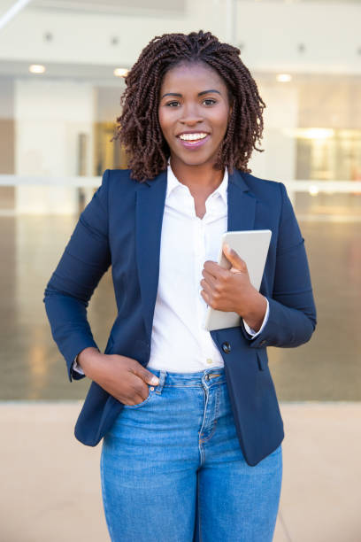 Young businesswoman with tablet pc smiling at camera stock photo