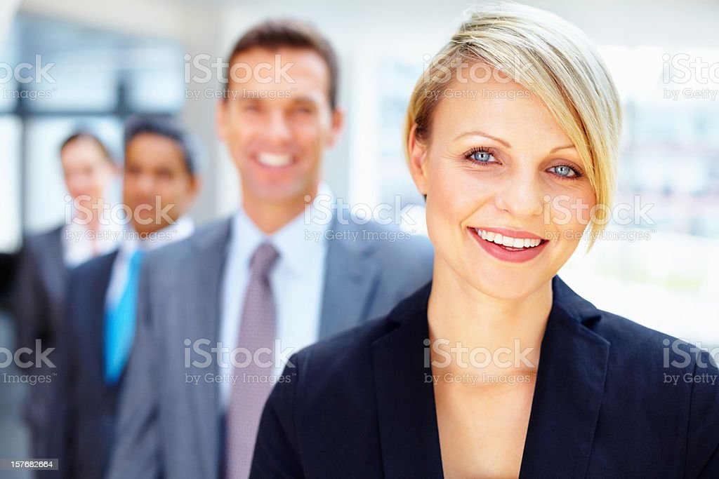 Young businesswoman with team in the background royalty-free stock photo