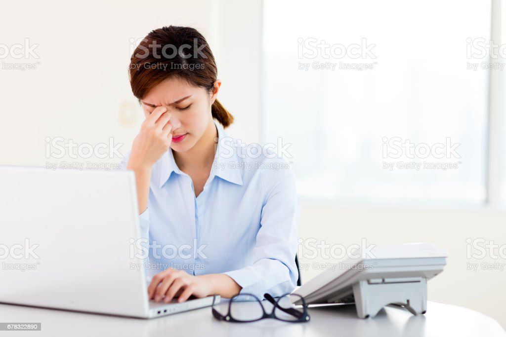Young businesswoman with tired eyes and headache stock photo