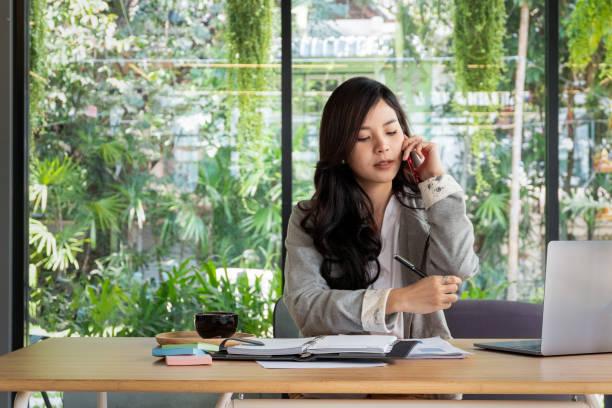 Junge geschäftsfrau Arbeit mit Mobiltelefonen und Notebooks im Büro, Business-Konzept – Foto