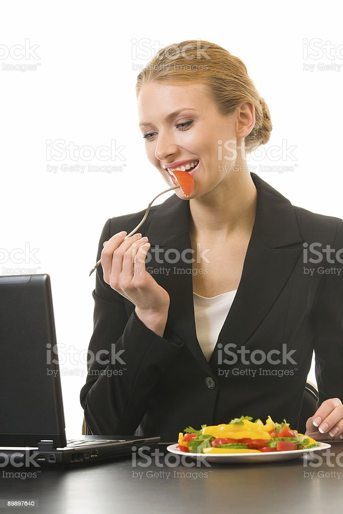 Young businesswoman working and eating salad at workplace royalty-free stock photo