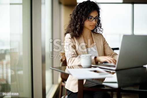 Young businesswoman working on laptop at a cafe