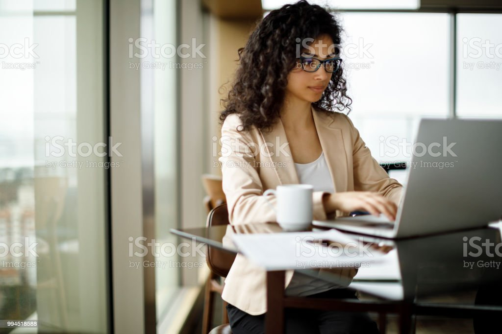 Young businesswoman working on laptop at a cafe stock photo