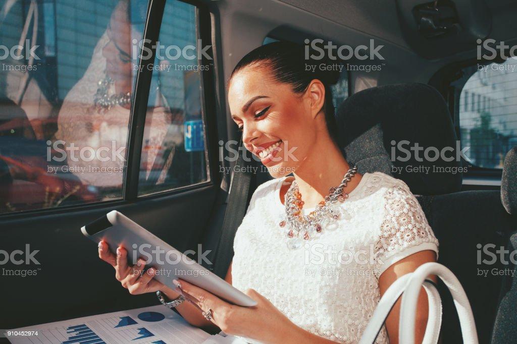 Junge Geschäftsfrau arbeiten mit digital-Tablette auf dem Rücksitz des Autos – Foto