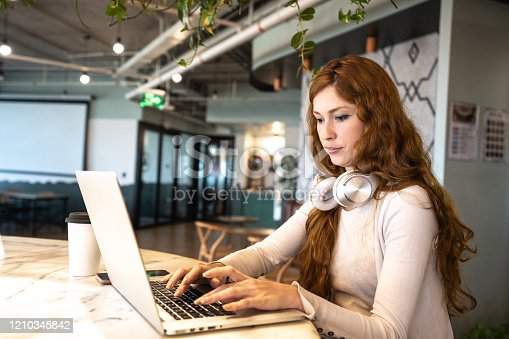 1031394390 istock photo Young businesswoman working with laptop at coworking 1210345842