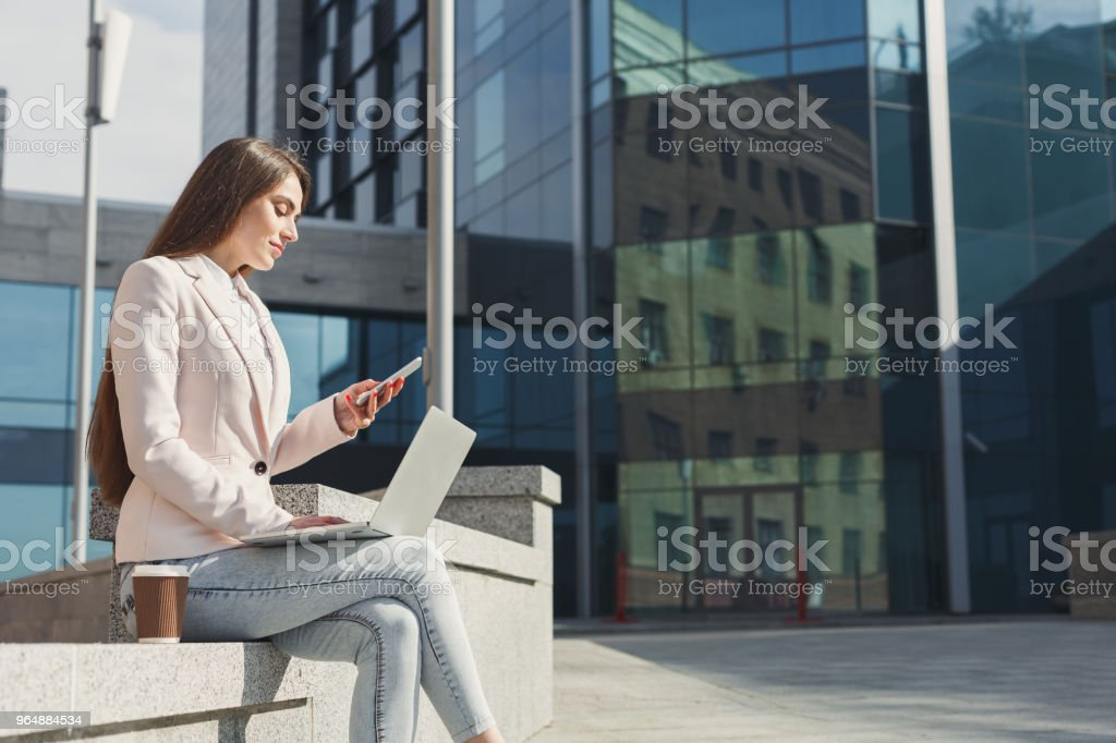 Young businesswoman working with laptop outdoors royalty-free stock photo