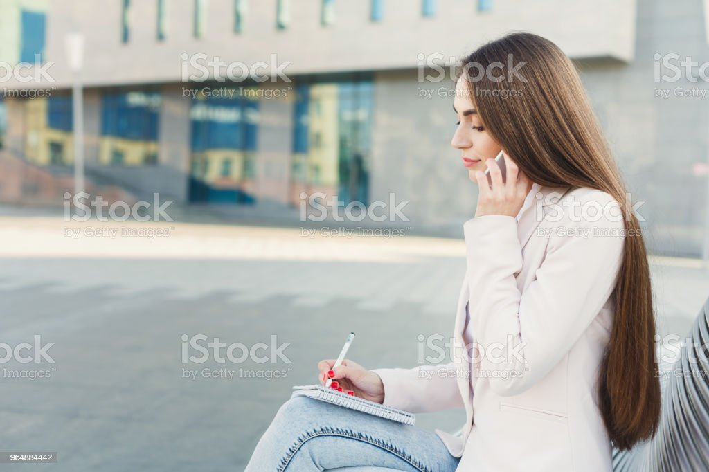 Young businesswoman working with papers outdoors royalty-free stock photo