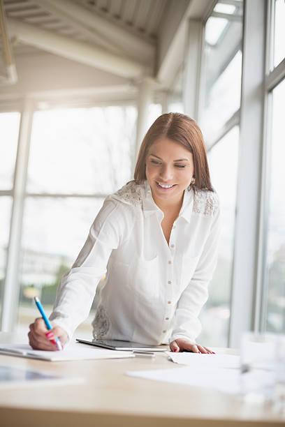 Junge Geschäftsfrau schreibt auf Papier am Schreibtisch – Foto