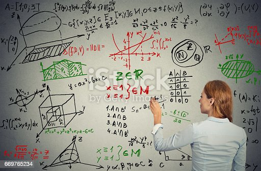 istock Young businesswoman writing on grey wall complicated formulas text graphic calculations 669765234