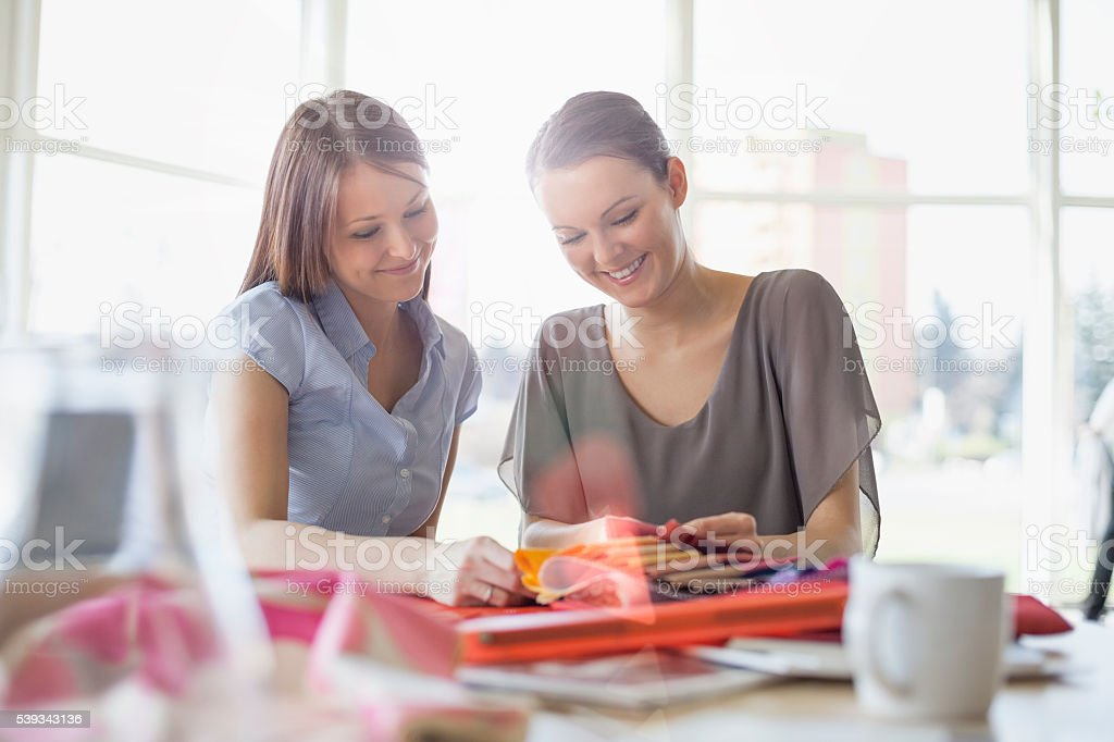 Young businesswomen discussing over fabric swatches in office stock photo