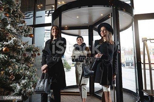 Young elegant businesswomen in winter coats entering a hotel through a revolving door.